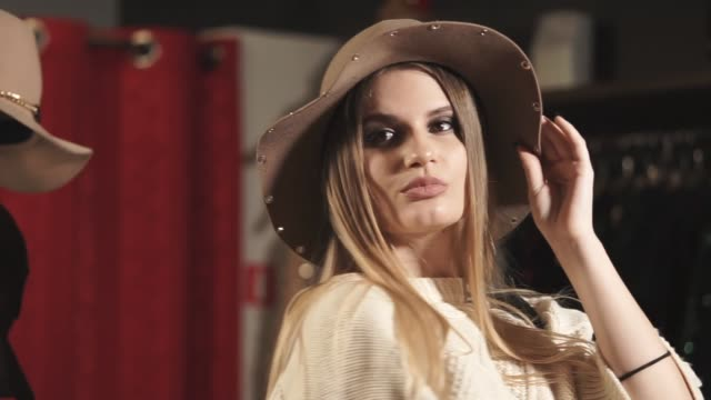 A young and pretty woman trying on a hat with fields in a trendy boutique video
