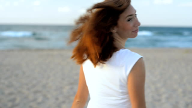 Young and seductive woman at 30s ealking at the beach and enjoying the sunset I video