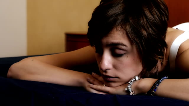 young and sensual woman on the bed reflects on her relationship - bassino video stock e b–roll