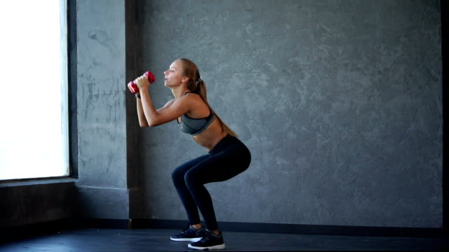 young and sporty woman makes a leap from squat with dumbbells in hands - giuntura umana video stock e b–roll