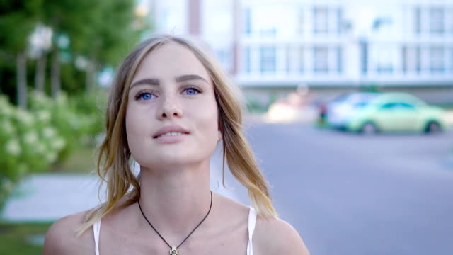 Young and unbelievably beautiful blonde woman with sky-blue eyes in white dress walks down the alley and nicely smile while combing her hair video