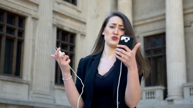 junge wütend und ängstlich frau weint, während ihr telefon schaltet aufgrund der entladenen batterie in der stadt - niedrig stock-videos und b-roll-filmmaterial