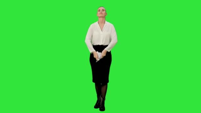 Jonge boze vrouw scheurt een vel papier en gooit het naar de camera op een groen scherm, Chroma Key video