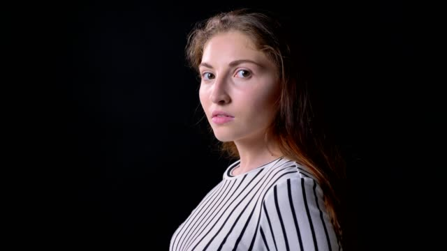 Young anxious woman turning head and looking at camera, standing isolated on black background, serious and confident