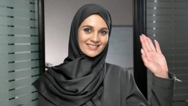 A young Arab girl in a hijab waving her hand, a gesture of greeting, hi, hello in office. 60 fps video