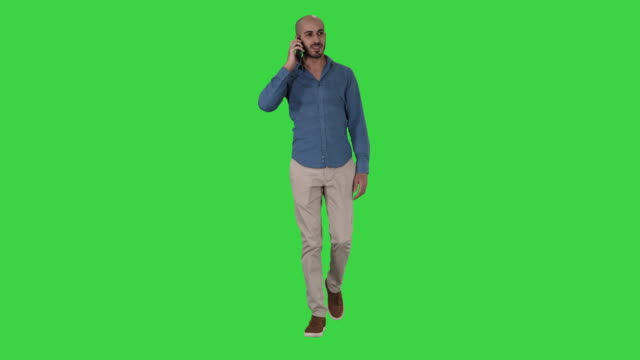 Young arab man walking and talking on the phone and smile on a Green Screen, Chroma Key Full length shot. Young arab man walking and talking on the phone and smile on a Green Screen, Chroma Key. Professional shot in 4K resolution. 011. You can use it e.g. in your commercial video, business, presentation, broadcast full length stock videos & royalty-free footage