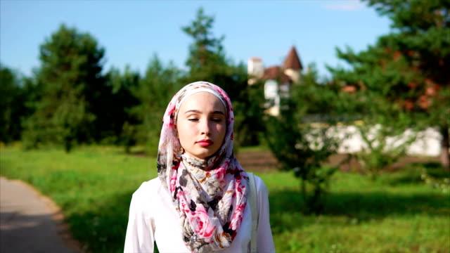 ung arabisk kvinna promenader i parken bära en hijab i en modern stad - anständig klädsel bildbanksvideor och videomaterial från bakom kulisserna