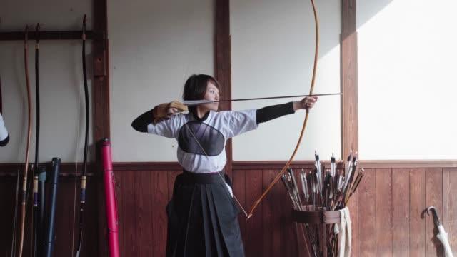 young archer practicing the japanese art of kyudo - tradycja filmów i materiałów b-roll
