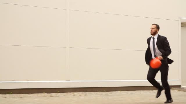 Jovem arquitecto em um terno de negócio correndo através de um local de construção. Câmera lenta - vídeo
