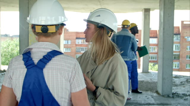 Young architecture and female worker talking at open air construction site Young architecture and female worker talking at open air construction site. Close up. Professional shot in 4K resolution. 104. You can use it e.g. in your commercial video, business, presentation, broadcast video craftsman architecture stock videos & royalty-free footage
