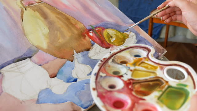 A young artist in an art workshop draws a still-life from nature in watercolor video