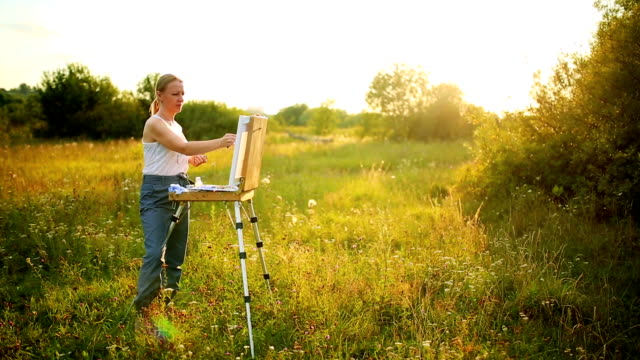 Young artist painting an autumn landscape video