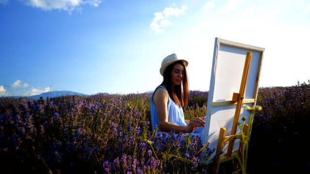 young artist painting an floral landscape - tavolozza video stock e b–roll