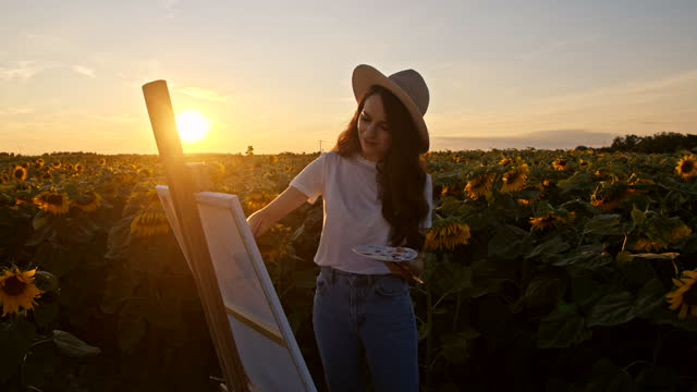 SLOW MOTION Young artist painting in the middle of sunflower field