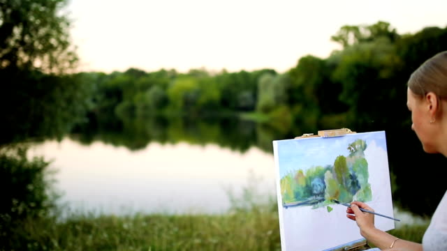 young artist painting picture in park with brushes and colors sitting by the romantic lake and urban buildings in background. ultra wide angle view video