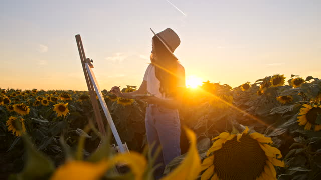SLOW MOTION Young artist painting sunflowers in nature