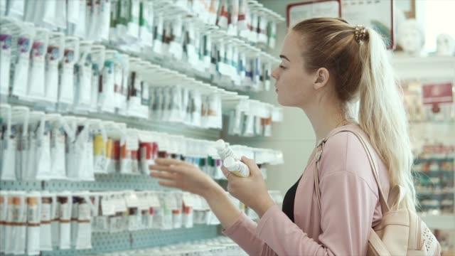junge künstlerin frau prüft röhren mit farbstoffen in einen professionellen shop - haartönung stock-videos und b-roll-filmmaterial