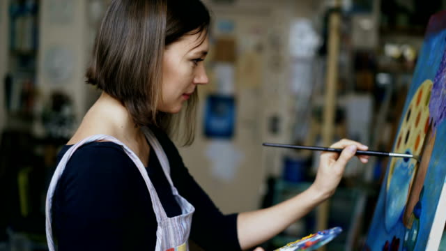 Young artist woman painting still life picture on canvas in art-school video