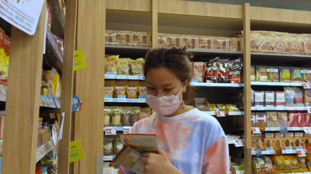 Young Asain woman in tie dye T-shirt shopping food at supermarke