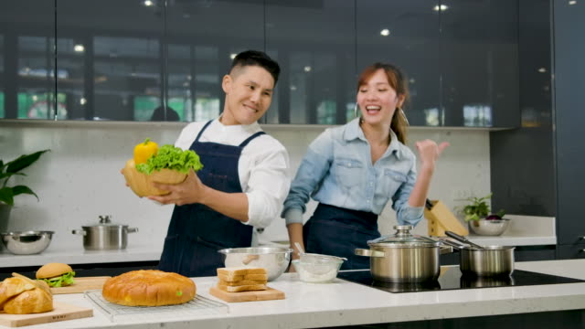 vídeos y material grabado en eventos de stock de joven pareja de asia se divierten bailando y cantando mientras se establece la mesa para el desayuno en la cocina en casa - dieta paleolítica