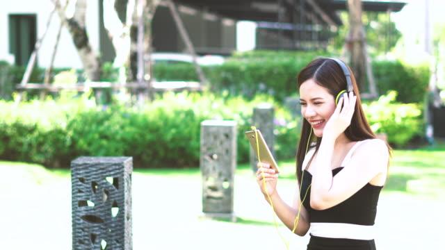 ung asien kvinna njuta av musik i trädgården - ligga på mage bildbanksvideor och videomaterial från bakom kulisserna