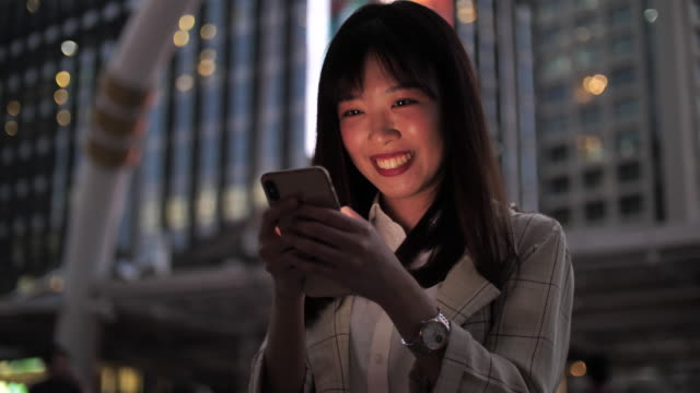stockvideo's en b-roll-footage met jonge aziatische vrouw met behulp van tablet met mooie bokeh in uitzicht op de stad - oost azië