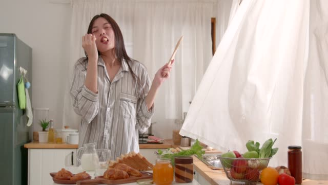 vídeos de stock e filmes b-roll de young asian attractive woman dancing in kitchen, eating some bread, morning time, smiling, lifestyle, natural beauty, feeling comfortable at home. - comida asiática