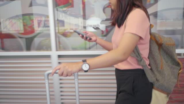 stockvideo's en b-roll-footage met jonge aziatische backpacker vrouw lopen in de luchthaven. - vliegveld vertrekhal