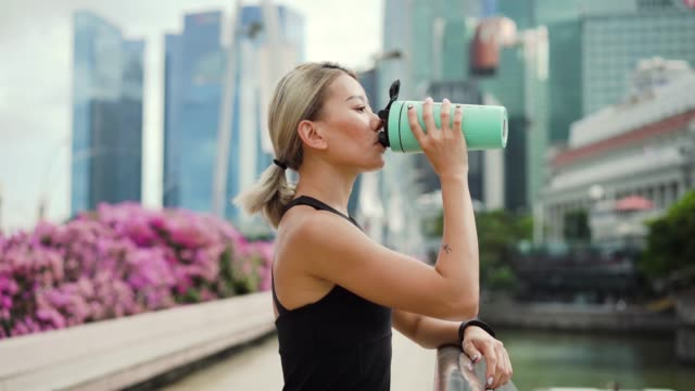 , young asian beautiful woman drinking water during workout