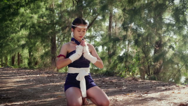 Young Asian boxer woman or Muay Thai praying ritual before the fight at outdoors, Thai boxing and Martial arts concept