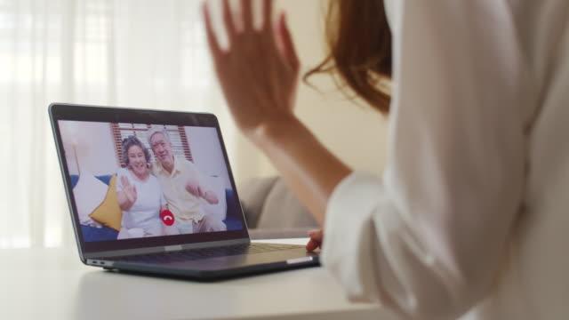 リビングルームで自宅で仕事をしながら、家族のお父さんとお母さんと話すラップトップビデオ通話を使用して若いアジアのビジネス女性。 - 人里離れた点の映像素材/bロール