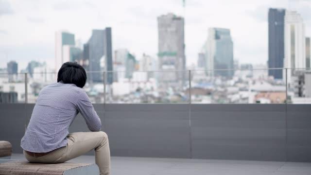 オフィスビル屋上テラスのベンチに座って仕事や人生の問題のストレスと不満を感じて若いアジア ビジネス男。バック グラウンドでのシティー ビュー。大鬱病性障害の概念。 - 悩む点の映像素材/bロール