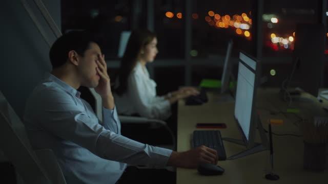若いアジアのビジネスマンは、仕事の残業後に疲れを感じています - 悩む点の映像素材/bロール