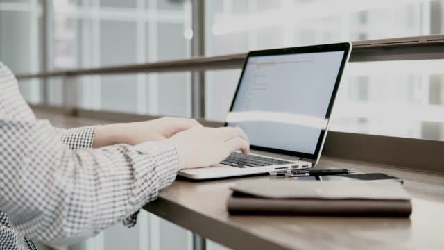 スマート フォンとノートブック木製机の上の作業スペースでラップトップ コンピューターを使用して若いアジア ビジネス男。男性の手は、ノート パソコンのキーボードで入力します。デジ ビデオ