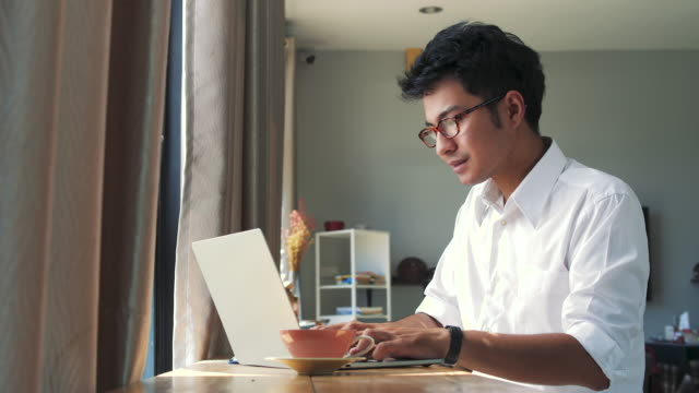 young asian business man working with laptop computer while sitting in coffee shop cafe - sud est asiatico video stock e b–roll