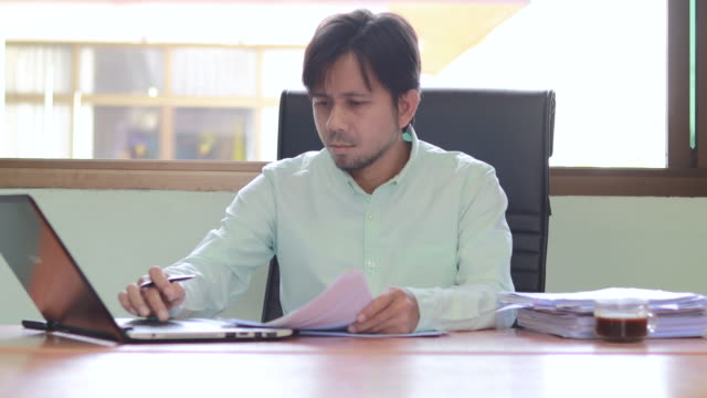 Young asian business man working with laptop documents sitting at office desk, financial analyst Young asian business man working with laptop documents sitting at office desk, financial analyst casual clothing stock videos & royalty-free footage