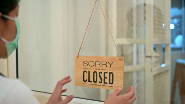 Young Asian business owner coffee shop wearing face surgical mask turning cafe shop sign to close due to business crisis from coronavirus outbreak problem.