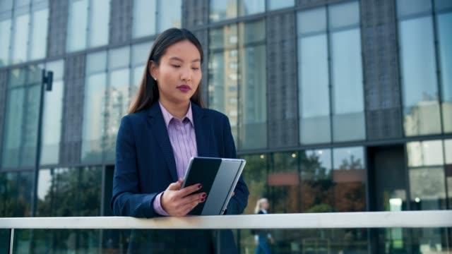 stockvideo's en b-roll-footage met ds jonge aziatische zakelijke vrouw scrollen op haar tablet in de voorkant van een moderne business building - financieel district