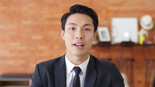 POV Young Asian businessman talking on video call or virtual meeting in office, front view, look at camera POV Young Asian businessman talking on video call or virtual meeting in office, front view, look at camera businesswear stock videos & royalty-free footage