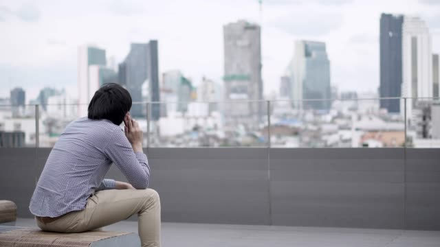 young asian businessman using smartphone for business talk sitting on office building rooftop terrace with city view in the background. business communication and corporation concepts. - terrazza video stock e b–roll