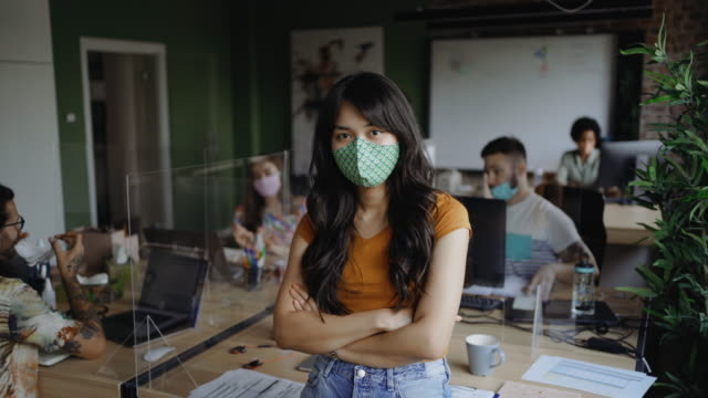 Young Asian businesswoman confidently posing with a face mask video