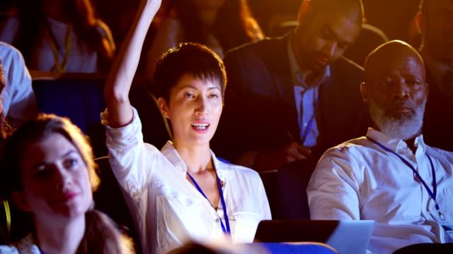junge asiatische geschäftsfrau erhebt hand in business-seminar im auditorium 4k - zuschauerraum stock-videos und b-roll-filmmaterial