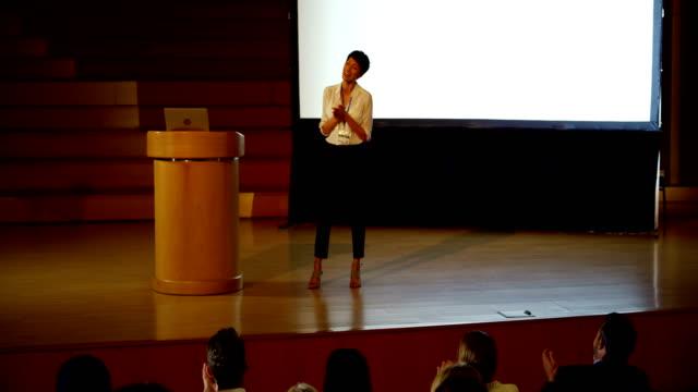 stockvideo's en b-roll-footage met jonge aziatische zakenvrouw spreken in business seminar in auditorium 4k - luidspreker