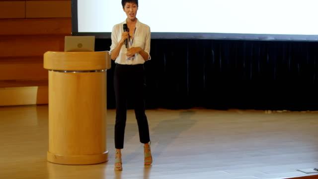 stockvideo's en b-roll-footage met jonge aziatische zakenvrouw spreekt in spreker op het podium in auditorium 4k - luidspreker