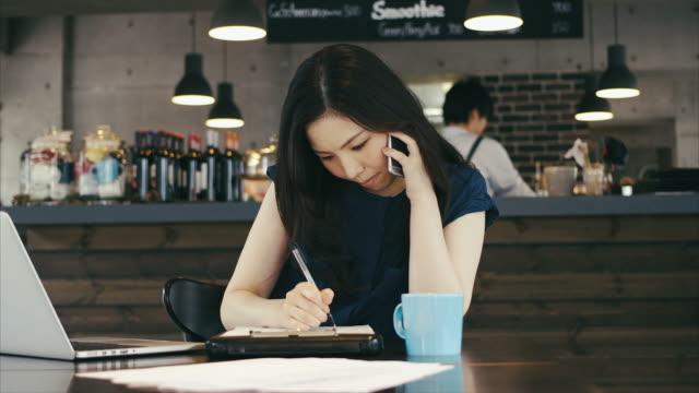 若いアジアビジネスウーマンのご注文を承っております。電話とノートパソコン - バーカウンター点の映像素材/bロール
