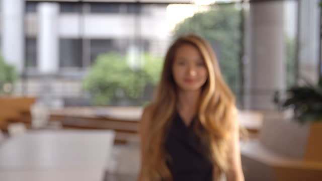 Young Asian businesswoman walking into focal plane video