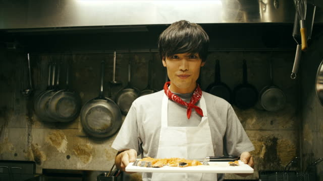 Young Asian Chef Holding Cutting Board with Salmon