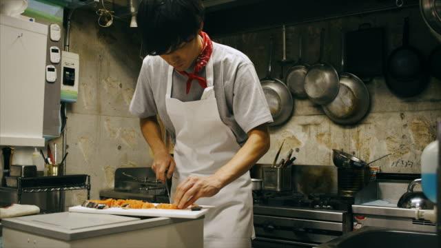 junger asiatischer koch in der küche schneiden lachs - sushi stock-videos und b-roll-filmmaterial