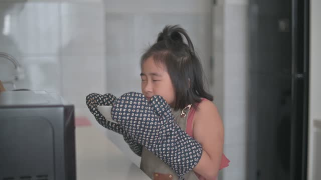Young asian chinese girl waiting and looking her food out from microwave using protective glove in kitchen