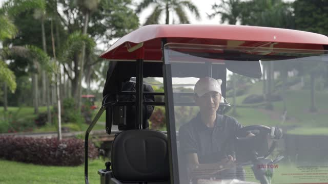 young asian chinese man golfer driving golf cart and unpacking equipment at golf course